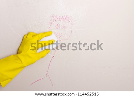 Gloved hand, cleaning crayon off wall with magic eraser - stock photo