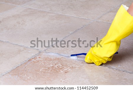 gloved hand cleaning tile grout with toothbrush - stock photo