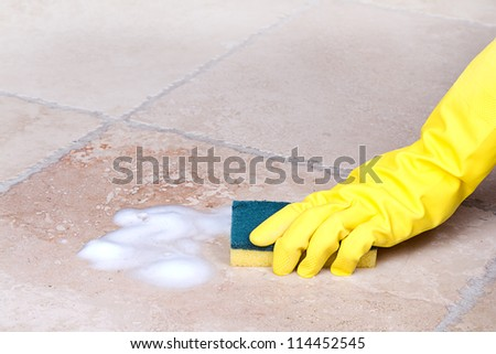 gloved hand cleaning tile with sponge - stock photo