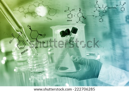 Gloved hand hold a beaker in laboratory room. - stock photo