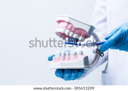 Gloved hand holding dental instrument - stock photo