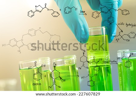 Gloved hand holding the test tubes, with chemical reaction, in the laboratory - stock photo