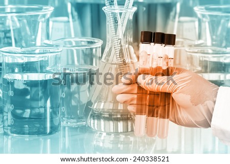Gloved hand holding the test tubes with glassware in laboratory - stock photo