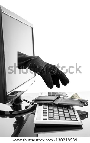 Gloved hand of a thief stealing wallet through a computer screen. Concept of internet crime. - stock photo