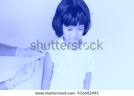 Gloved hand of nurse making an injection to little girl with effect blue  tone style - stock photo