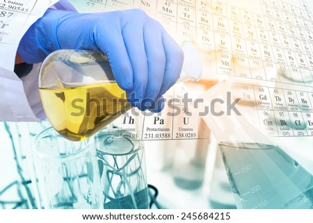 Gloved hand pour the solution from flask to another one in laboratory with periodic table background. - stock photo