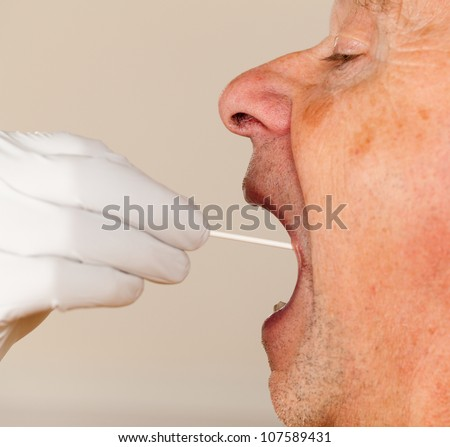 Gloved hand taking a bodily fluid sample for DNA test from senior male person - stock photo