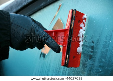 Gloved hand using an ice scraper on iced glass - stock photo