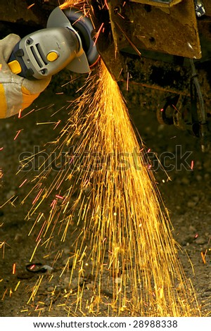 Gloved hand using grinder in motion - stock photo