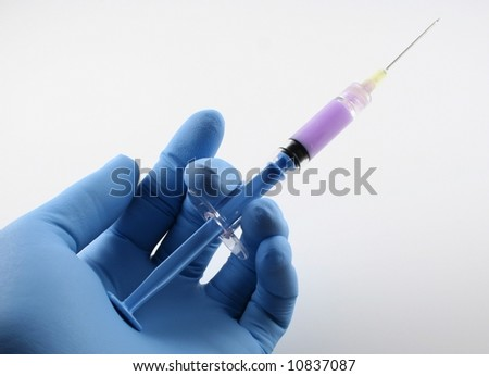 gloved hand with filled blue syringe with needle - stock photo