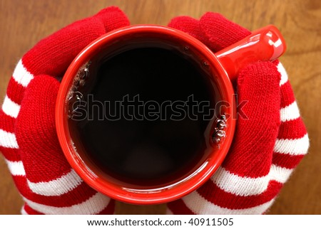 Gloved hands holding mug filled with hot beverage.  Macro with shallow dof.  Copy space inside mug. - stock photo