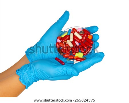 Gloved hands with colorful pills  - stock photo