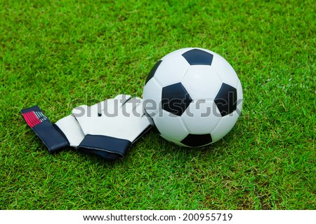 Gloves and football on the green grass. - stock photo