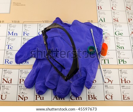 Gloves, glasses and chemical on aperiodic table. - stock photo