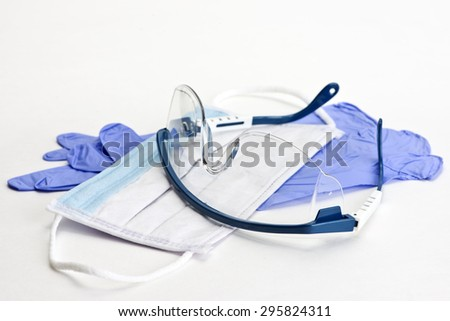 Gloves, mask and safety glasses for personal protection during medical procedures. - stock photo