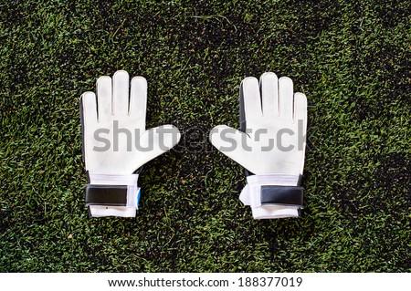 Gloves on soccer field - stock photo