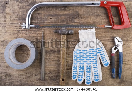 gloves saw tape hammer on the wooden table - stock photo