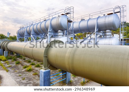 Glow light of petrochemical industry water tank on sunset. - stock photo