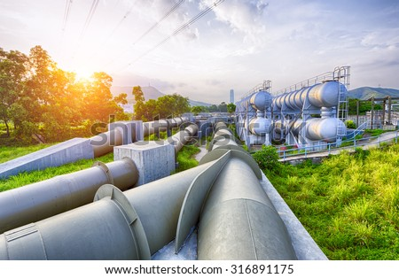 Glow light of petrochemical industry water tank on sunset - stock photo