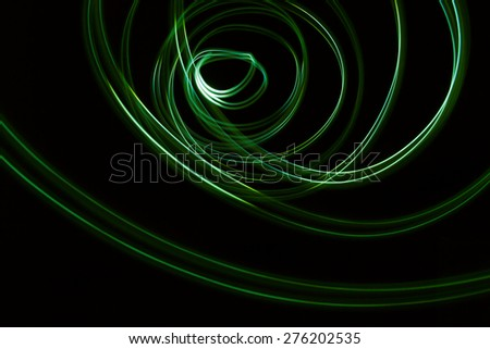 Glowing abstract curved lines. Green colors. Black background. Done by long exposure technique - stock photo