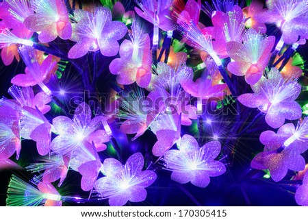 Glowing abstract multicolored flowers on a dark background - stock photo