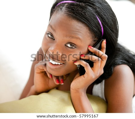 Glowing afro-american teenager talking on phone smiling at the camera lying on a sofa against white background - stock photo