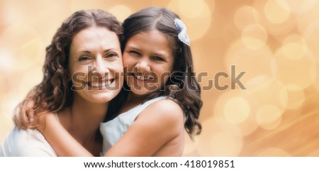 Glowing background against happy mother and daughter smiling at camera - stock photo