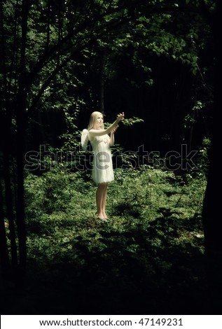 Glowing blonde in dark forest with angel wings in white with selective focus
