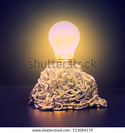 Glowing bulb in ball of chains - stock photo