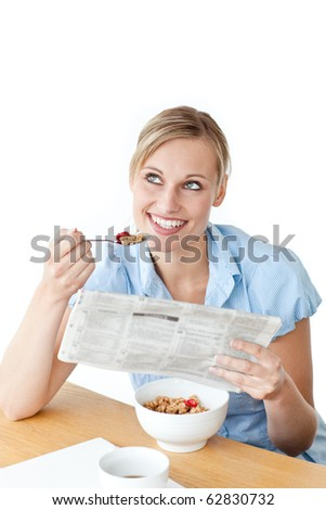 Glowing businesswoman having breakfast and reading a newspaper sitting against a white background