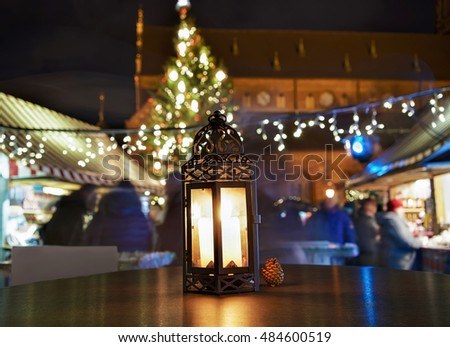 Glowing candle lantern on the table at the Christmas Market in Riga, Latvia in the evening. Illuminated with light.