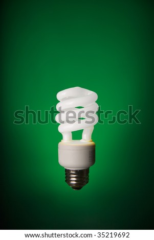 Glowing CFL light bulb on green background - stock photo