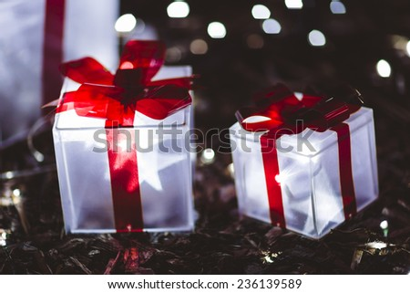 Glowing Christmas gifts under tree - stock photo