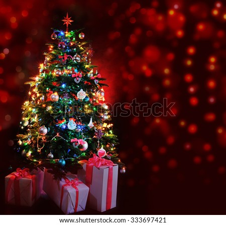 glowing Christmas tree with gifts on dark red background - stock photo