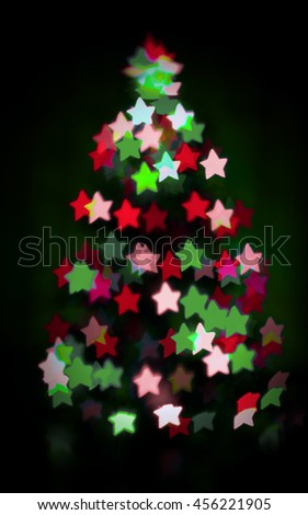 glowing christmas tree with star bokeh on dark background