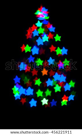 glowing christmas tree with star bokeh on dark background - stock photo