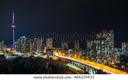 Glowing cityscape and buildings as light streaks along the Gardiner Expressway on a hot & muggy summer night in Lakeside Toronto, Canada.