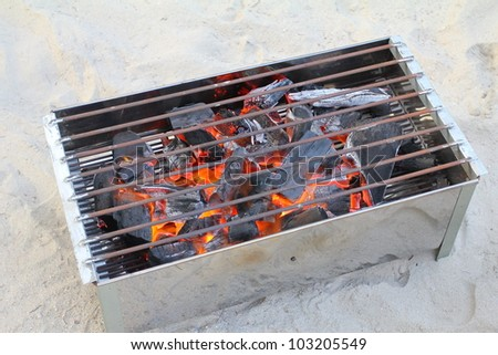 Glowing coals and fire flames in fireplace with metal grating - stock photo