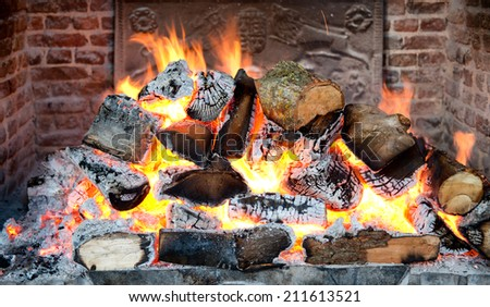 Glowing coals in a wood fire with fiery orange flames in a brick hearth or fireplace with a wrought iron backplate, close up backgroud view - stock photo