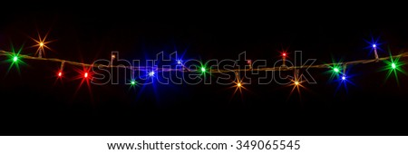 glowing colorful Christmas lights on black background - stock photo