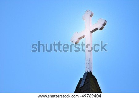 Glowing cross atop a steeple against a blue sky - stock photo