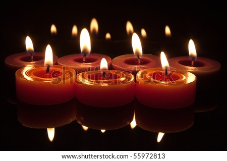 glowing flames from candles with reflections top and bottom
