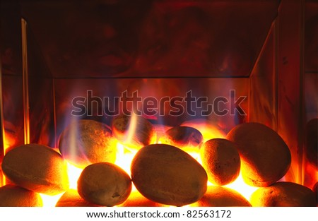 Glowing gas fire with flames. Stones glow white hot in this fireplace. - stock photo