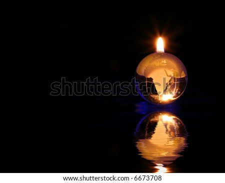 Glowing Glass Globe on Black Background With Flame - stock photo