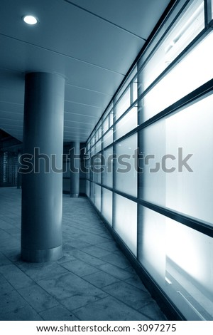 Glowing glass in modern building facade with white light from inside - stock photo