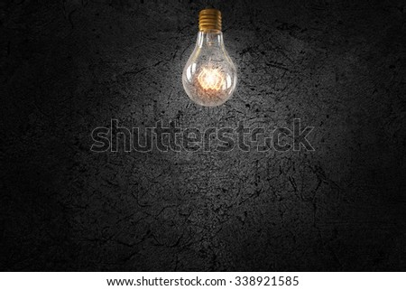 Glowing glass light bulb on concrete background - stock photo