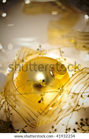 Glowing golden Christmas ornaments with translucent ribbons, sparkling gold stars and twinkling white lights. Short depth of field with glowing effects and dark vignette. - stock photo