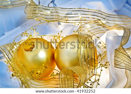 Glowing golden Christmas ornaments with translucent ribbons, sparkling gold stars and twinkling white lights. Short depth of field with glowing effects. Good for Christmas card or background. - stock photo