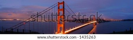 Glowing Golden Gate bridge on a stormy evening in winter. Blue dusk with departing storm clouds contrast with the San Francisco skyline lit by thousands of lights. Traffic flows as two-colored river. - stock photo