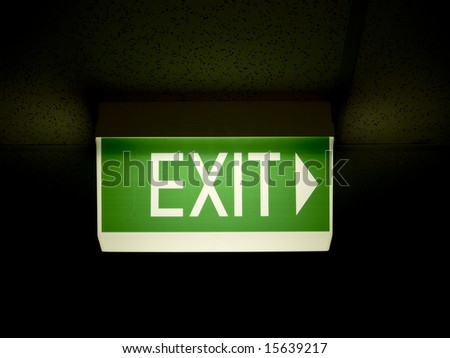 Glowing Green emergency exit sign - stock photo
